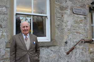 De ja vu: Former Village Hall treasurer John Geldard stands outside the venue just as he did more than 50 years ago upon its launch.